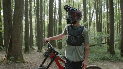 A Mountain Biker Standing in a Forest