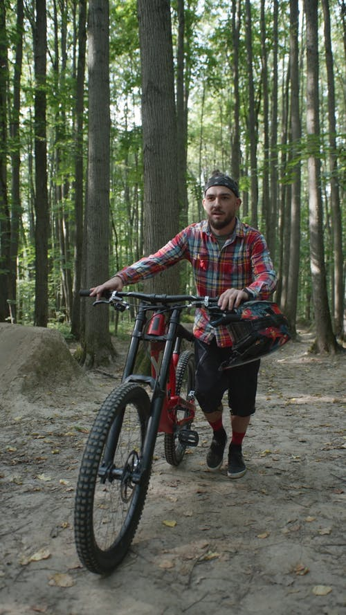 A Man Walking With His Bike in a Forest