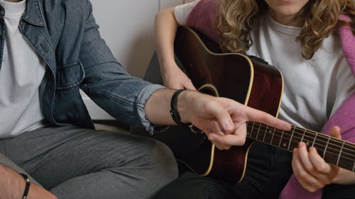 A Man Teaching a Woman How to Play a Guitar