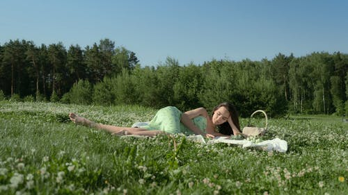 Woman Lying on a Picnic Blanket While Reading a Book