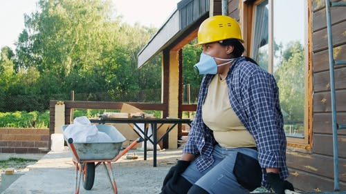A Woman Removing His Face Mask and Hard Hat