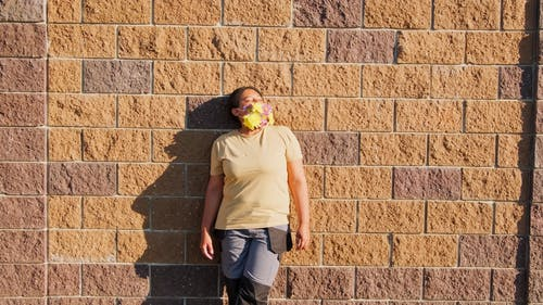 A Woman Wearing Face Mask With Flower Design Leaning on the Wall