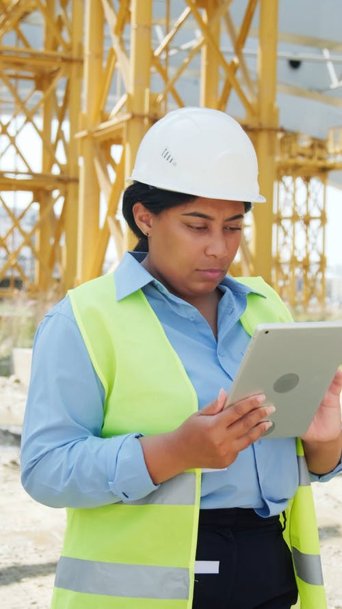 A Woman in a Construction Site Using Tablet