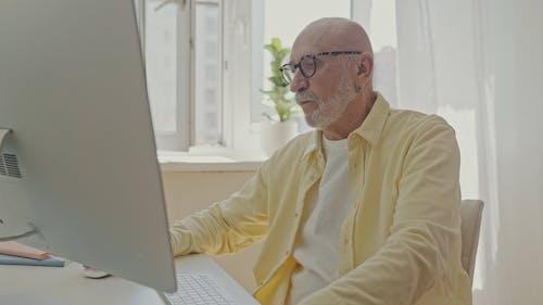 An Old Man Using a Computer