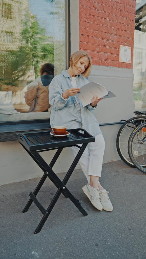 An Elderly Woman Sitting while Reading Magazine