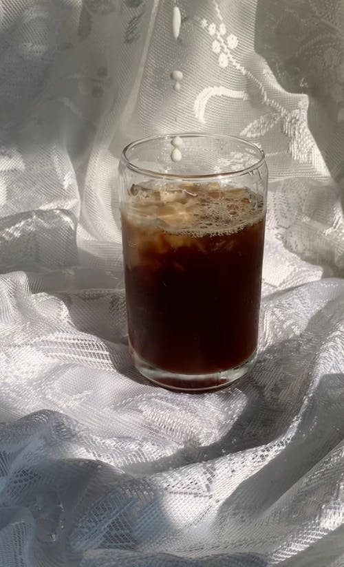 A Person Pouring Milk on a Glass of Iced Coffee