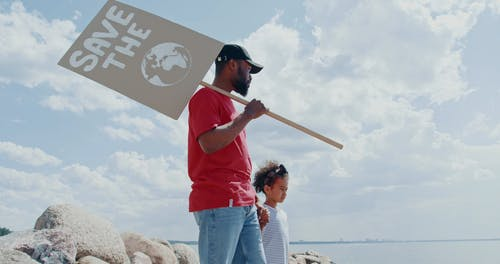 A Father Holding His Daughter and a Placard