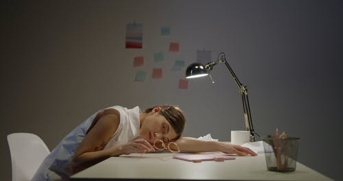 An Exhausted Woman Leaning on her Work Desk