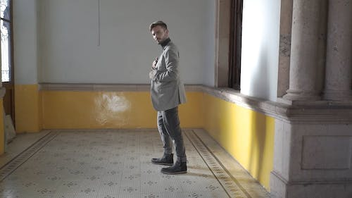 A Stylish Man Standing While Looking at Camera