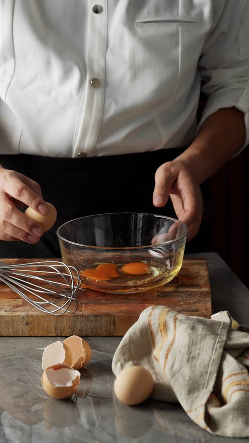 A Person Cracking an Egg on a Glass Bowl