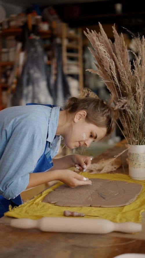 A Woman Designing a Clay