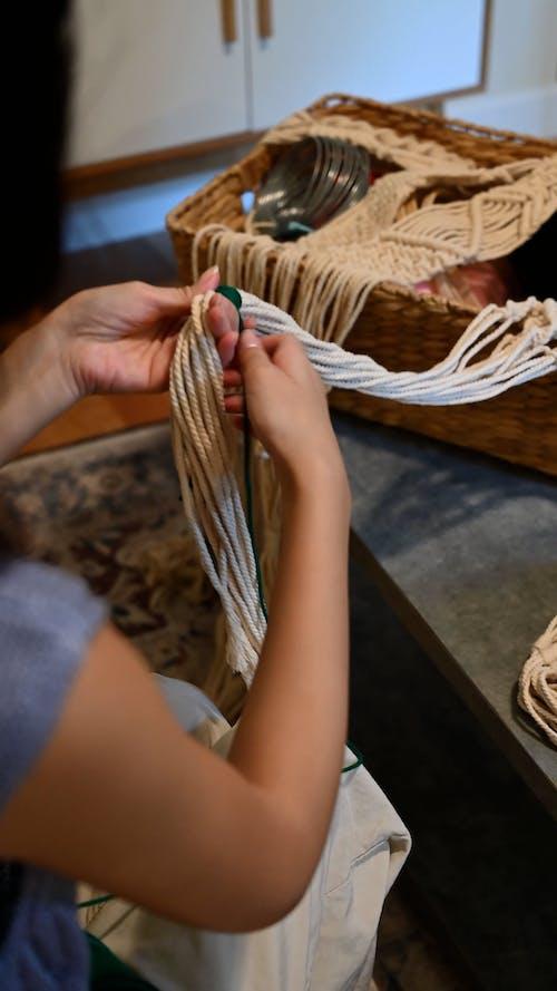 A Woman Tying Green Yarn on Threads