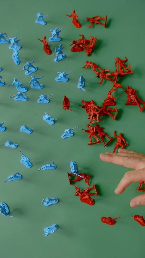 A Person Flicking Plastic Toy Soldiers