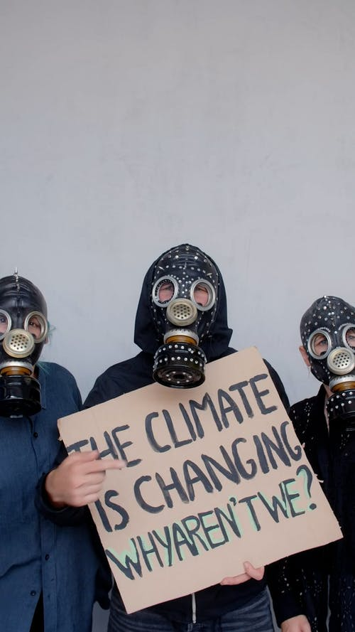 People Wearing Gas Masks Holding a Placard