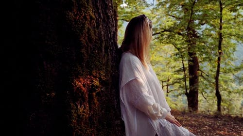 Woman Leaning Against a Tree Trunk