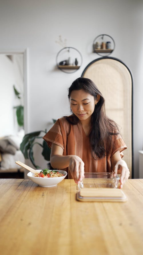 A Woman Putting Pasta on a Rectangular Glassware