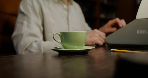 A Man Using Typewriter while Drinking Coffee