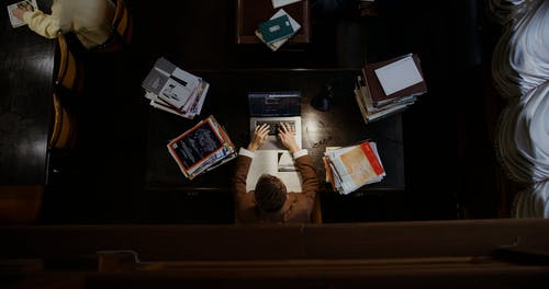 A Man Closing His Book and Laptop After Working
