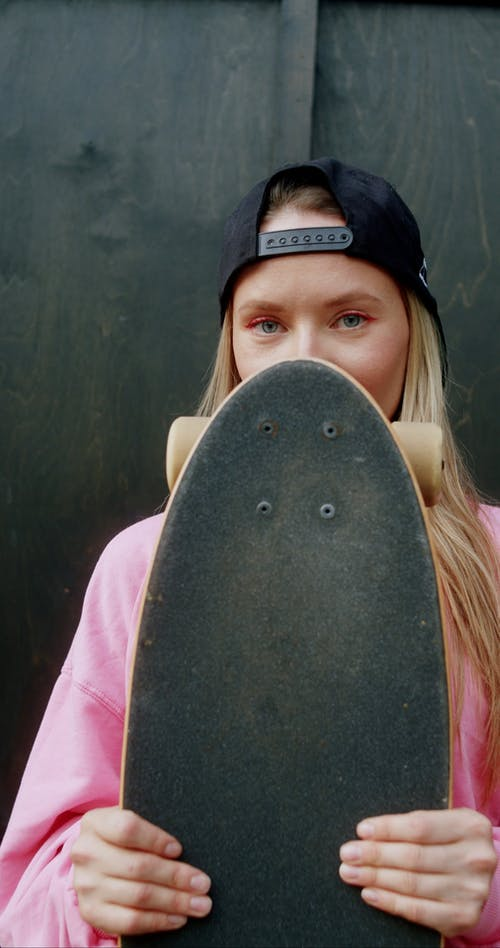 Beautiful Woman Holding a Skateboard
