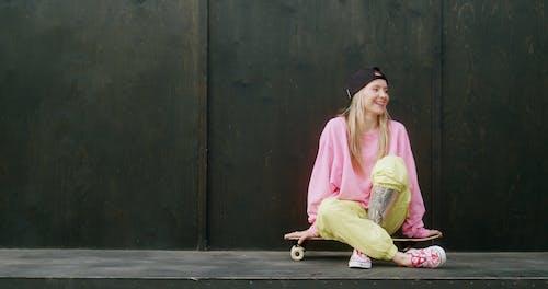 Stylish Woman Sitting on a Skateboard