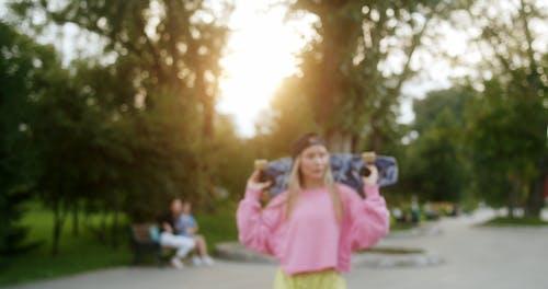Woman Carrying a Skateboard