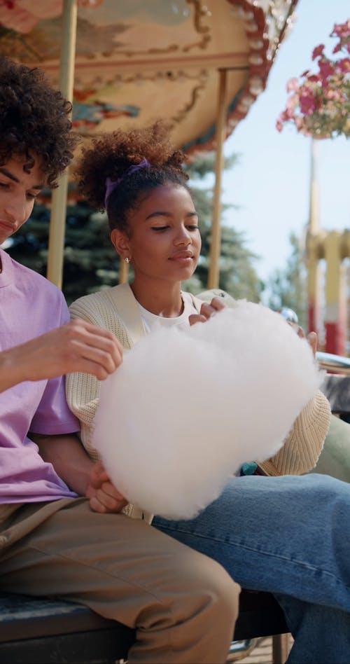 Smiling Teenagers Eating Cotton Candy and Chatting
