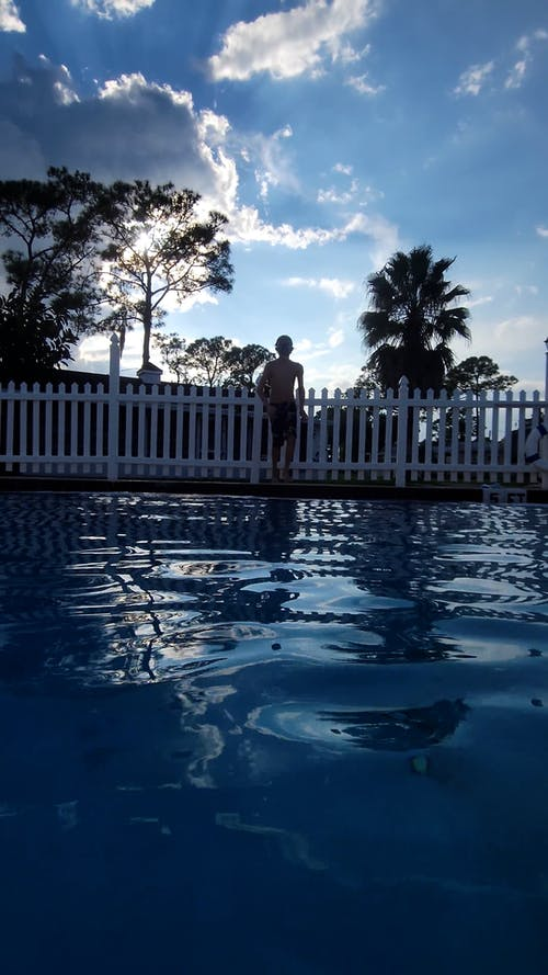 A Young Boy Jumping Into the Swimming Pool