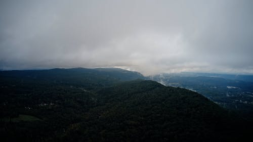 Aerial view on forests on hills and clouds moving over them
