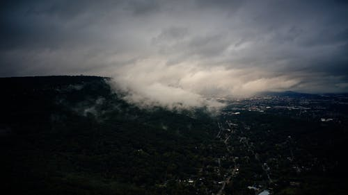 Clouds moving over forests near town