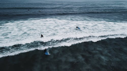 Drone footage of surfers in blue sea