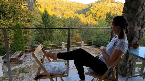 Smiling girl sitting on chair and looking at forest