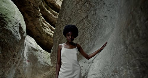 A Woman Standing in a Cave While Seriously Looking at Camera