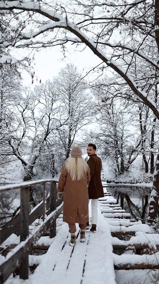 A Couple Walking On A Hanging Bridge