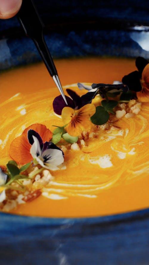 A Person Putting Garnish on a Pumpkin Soup