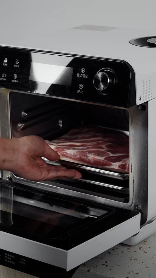 Person Putting Raw Meat into Electric Stove