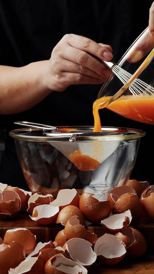 Cook Pouring Eggs Through Filter