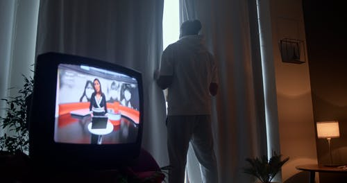 TV and Man Looking Through Window