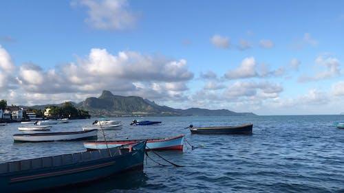 Boats in Ocean Against Mountain