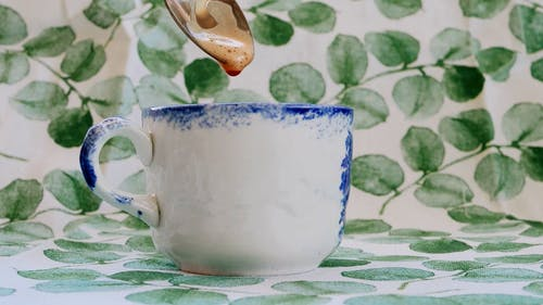 Close-up of Spoon Dipping in Coffee Cup