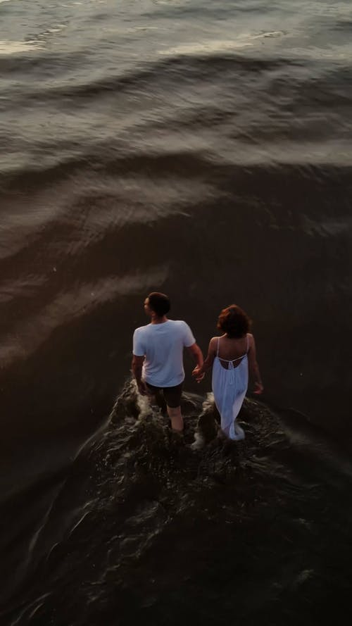 Drone Footage of a Couple Holding Hands while Walking in Shallow Water
